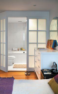 Trocado a parede do banheiro por três painéis de vidro jateado, dando mais luminosidade ao quarto