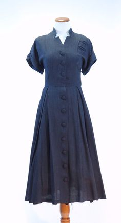 A beautiful classic 1940's dress with charcoal gray pin stripes and covered button closure all the way down the front. Features a unique cut out mandarin style collar, short cuffed sleeves, two faux p