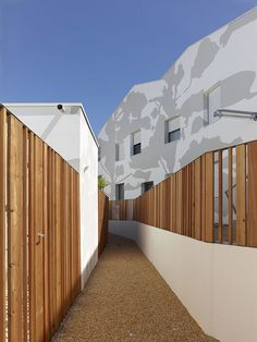 French architecture practice Tetrarc has applied acamouflage print onto the walls of this social housing complex in Saint-Gilles Croix de Vie to create theimpressionof shadows cast by trees.