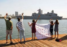SAN DIEGO(May 14, 2013)Family members of Capt. Putnam Browne,commanding officer of amphibious transport dock ship USS Green Bay(LPD 20),wave to welcome the ship as she returns to Naval Base San Diego as part of Peleliu Amphibious Ready Group.The ready group returning from a W Pacific deployment where they performed maritime security operations,theater cooperation efforts & op support in the U.S. 5th and 7th Fleet areas.(U.S. Navy photo by Mass Communication Specialist 2nd Class Rosalie…
