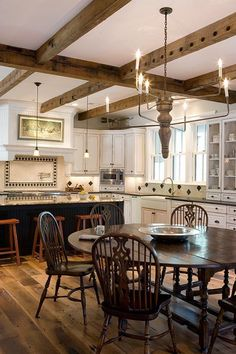 Love the big round table, with Windsor chairs, in the middle of the kitchen.