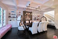 The formal dining room features two black and white canopy hood chairs along with six additional leather slipper chairs. The high-end seating is gathered around a black farmhouse table.