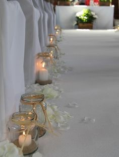 Mason jars with candles and sand, neck wrapped with raffia, as wedding aisle decorations. | Anderson Jones Photography