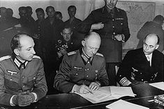General Alfred Jodl, Chief of the Operations Staff in the German High Command, signs the document of unconditional German surrender at General Eisenhower's Headquarters in Reims, France, May 7, 1945. On Jodl's left is Admiral Von Friedeburg of the German Navy, and on his right is Major Wilhelm Oxenius of the German General Staff.