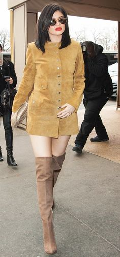 Kylie Jenner wears a suede coat as a dress, thigh-high suede boots, a suede clutch, and clear-frame sunglasses