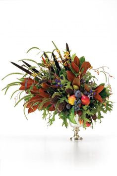 This centerpiece makes a strong statement with oak and magnolia leaves, bittersweet, pine cones, pheasant feathers, and fruit.