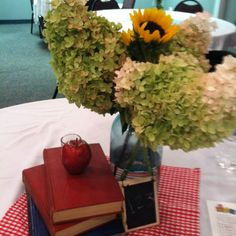 Easy school themed centerpiece with old books, mason jar, apple, hydrangeas and sunflowers