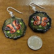 These handmade paper mache, Austrian crystal, and sterling silver dangle earrings feature a hand painted picture of red and black butterflies with white flowers and a shimmering goldtone and black background. #PaperMache #Earrings #handmade #IowaCity #Jewelry