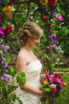 bride at floral ceremony arch via http://mountainsidebride.com