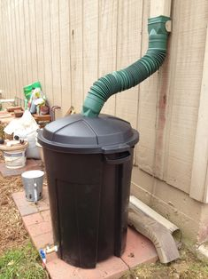 Rainwater collection. Duh... a cheap garbage can to collect rainwater--have been trying to think how to do this affordably. And the bendy green thing is cheap...