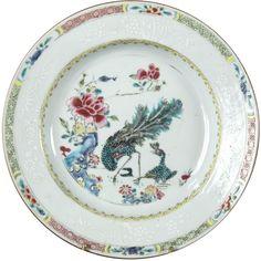 Assiette peinte dans les émaux de la famille rose à décor de paons en porcelaine de Chine de la Compagnie des Indes d'époque Yongzheng. Assiette peinte dans les émaux de la famille rose de deux paons près d'un rocher percé et d'un buisson de pivoines. Sur le marli, frise de fers de lance peinte en jaune.