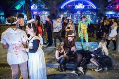 Costumed revellers, one of whom appears to be sleeping on the pavement, spill onto the str...