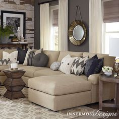 We love all the contrast in this living room! The contemporary clean lines of the sofa contrast the rustic wood wall, giving the room a great mix of styles while still matching. This room also incorportates gray and brown tones perfectly, which is a tricky thing to do. The gold round mirror and unique coffee table add interest while not drawing the eye away from the rest of the characteristics.