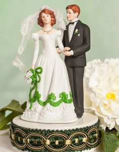 <p> This beautiful cake topper will be the perfect accent for your wedding that reflects your Irish heritage. The bride's dress is accented with a green shamrock design. The base features an elaborate celtic knot trim all the way around the base. Made of porcelain. </p>