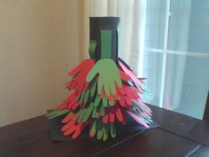 Hands up Christmas tree. Trace a childs hand on to Red and Green construction paper, cut out the childs hand print. Take a sheet of black construction paper and tape the sides together to form a circle then tape to a second sheet of black concrustion paper to get it to stand up. The tape the two black sheets of construction papers together. Next tape or glue the hands on you can ither cut green strips of construction paper to tape or glue the hands on or you can skip the green strips.