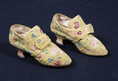 A pair of 18th century needleworked shoes: Worked to a yellow ground, with central pink rose design to the toe of the shoes, with further scrolling foliage and flowers in reds and blues; leather covered Louis heels, and straps across fronts for buckles.
