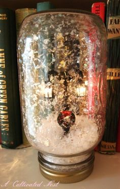 "Super easy WATERLESS snow globe! ""Basically you just glue whatever it is that you want in your globe to your lid, fill the jar with some fake snow, screw the lid on, turn it upside down and  you have a waterless snow globe."" She uses a battery operated miniature lamp post here. #ChristmasCraft #ChristmasDIY"