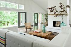 Airy white living room of a Brush Prairie House in southern Washington state grounded by a leather sectional and peekaboo painted brick hearth. | Interior design by Jessica Helgerson Interior Design (lead: Jesse Moyer).