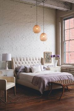 Loft bedroom, brick walls and hanging lamps.
