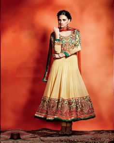 A georgette ensemble in dark beige with a tinge of brown.Floral embroidery on sleeves and broder with hues of orange,green,gold and red.Bright orange dupatta in Chiffon fabric.