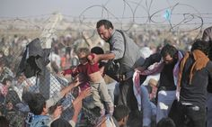 A June 14, 2015 file photo of a Syrian refugee carrying a baby over the broken border fence into Turkey after breaking the border fence and crossing from Syria in Akcakale, Sanliurfa province, southeastern Turkey. The mass displacement of Syrians across the border into Turkey comes as Kurdish fighters and Islamic extremists clashed in nearby city of Tal Abyad.