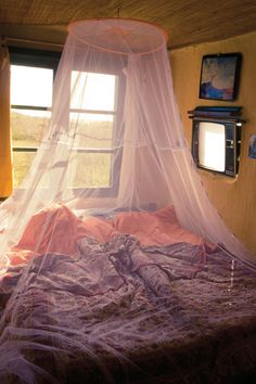 i have always wanted one of those above my bed for as long as i can remember. i don't care if it's just mosquito netting, it still feels magical.