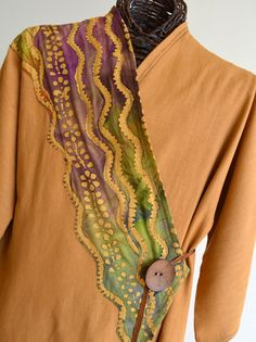 You'll be stepping up in these warm, flowing colors reminiscent of a canyon sunset. Hand dyed linen is accented with a diagonal batik design in front and back. A large, wooden button brings closure with a strap of warm, brown leather. The asymmetrical design is figure flattering for all body types. $188. - I would use yarns and ribbons and strings of beads for design