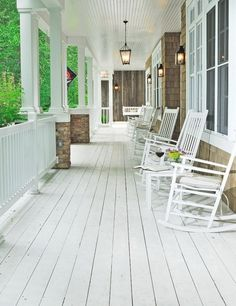 I love this porch... the lights, the colors, the stone, cedar shakes, and the white rocking chairs!