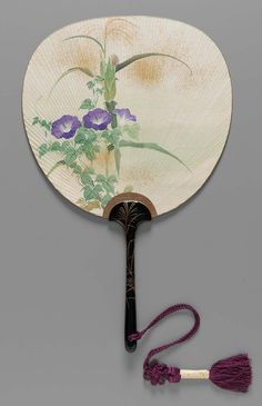 Painted paper leaf with bamboo foundation. Obverse: purple morning glories. Reverse: pink morning glories. Gold dusted over leaves. Gilt paper bilding; textured gold paper at handle. Black lacquered handle with painted gold and gray floral motif. Purple silk tassel depends from handle. Mate to 1976.432. In original papers and cardboard box.