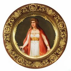 "Magnificent Royal Vienna hand painted porcelain portrait plate depicting Saint Mary Magdalene. Titled ""Madelaine"". This plate is intricately bordered with gilded laurel wreath, scenes with animals and scrolled floral designs over rust red background."