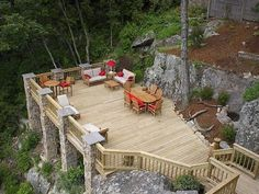 Backyard ideas. Sloped yard. Stone columns. Nice deck