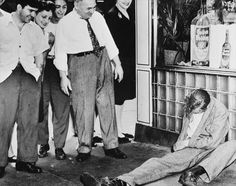 Not all Weegee's shots were morbid, however. Some were just plain comical. Here, a group converges around a passed out drunk outside a New York restaurant circa 1945.