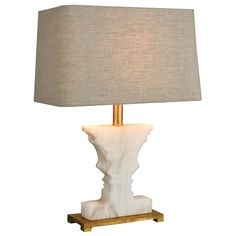 """With a nod to 1930's boudoir lighting, the Bayeux table lamp creates a grand presence in a poised living area or bedroom. Resting beneath a linen-hued shade, a carved silhouette emits an organic vibe in subtly veined alabaster. A gold-finished pedestal lends a perfectly posh finish. 15""""W x 9""""D x 21""""H. White alabaster, metal. Rectangular Sand linen hardback shade. Accepts a 150W maximum medium bulb (not included). 3-way switch."""