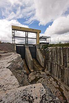 Image d'un ouvrage en béton avec des vannes et dont la partie la plus basse ressemble à un saut à ski qui mène à un corridor en roc.  L'évacuateur de crues Duplanter a une capacité maximale de 3 340 m3/s.  Situé sous l'appui Ouest du barrage KA-3, sur l'île Duplanter.