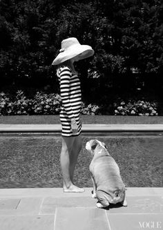 Dive In - In this last photo, I'm standing with our dog by the pool in the backyard. Our pool house, which is a tribute to the Beverly Hills Hotel and Indochine, is my husband's man cave. It's great because all his entertaining goes on outside the house. It's warm in the winter with the fire and pool friendly in the summer. In this photo: Lily is wearing a Minnie Mortimer dress, a hat by Kemble Interiors of Palm