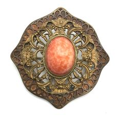 """Fishel Nessler Co Faux Coral Shield Brooch, Art Deco, 1920s to 1930s   Do you like gingerbread patina? Yes? This is the brooch for you! Made and signed by Fishel Nessler Co, set with a large faux coral glass cabochon and in excellent condition. The patina is a testimony to its long history. The shield-shapedbrooch has two layers, the smaller one on the top has open work. The cabochon setting is finished with a delicate twisted wire rope frame. It is square, measuring 2 1/4"""" by 2 1/4"""". The…"""