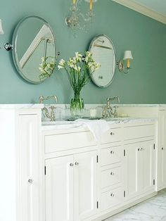 simple-turned-sophisticated farmhouse-style vanity was given a fresh coat of white paint and new hardware that consisted of cut-glass knobs and black hinges that hint at old wrought iron. The deep drawers and cabinets make storage easy and plentiful in this master bath. The countertop is covered with carrara marble, and bridge-style sink faucets give it a vintage feel.