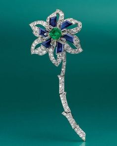 A Diamond, Emerald and Sapphire Flower Brooch, by Cartier Designed as a flower blossom, with a square-cut emerald pistil, enhanced by baguette-cut diamonds and calibré-cut sapphires, to the openwork circular-cut diamond petals and articulated circular-cut diamond stem, mounted in platinum and 18k gold