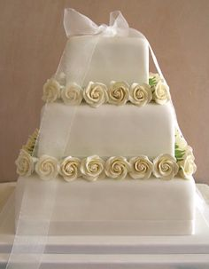 Three tiers of small decorated square wedding cakes with white roses and sheer ribbon
