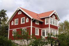 Rött hus med vita knutar och vacker veranda i två plan.