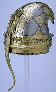 Indian (Maratha) helmet, 18th century, with pointed and curved-over crest and a curved tail projecting below rim. Partially gilt, leaving panels of steel. Helmet with pointed and curved-over crest and a curved tail projecting below rim. Partially gilt, leaving panels of steel.Helmet with pointed and curved-over crest and a curved tail projecting below rim. Partially gilt, leaving panels of steel. Height: 23 cm, Diameter: 25 cm, Victoria and Albert Museum.