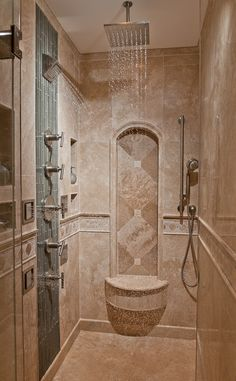 The Tile Shop: travertine shower with glass water accent.