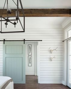 Cottage bedroom boasts a white shiplap wall fitted with a blue shiplap barn door. Cottage bedroom boasts a white shiplap wall fitted with a blue shiplap barn door on rails illuminat Sunroom Decorating, White Shiplap Wall, Home, Cottage Bedroom, House Design, New Homes, Farmhouse Paint, House Interior, Shiplap