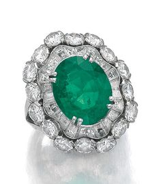 EMERALD AND DIAMOND RING, VAN CLEEF & ARPELS, 1959. The oval emerald, framed with circular-cut and tapered baguette diamonds, size 52, signed Van Cleef & Arpels and numbered, French assay and partial maker's marks, case stamped Van Cleef & Arpels.