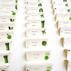 Escort cards with guest's names and a picture of the corresponding fruit or vegetable for each table.