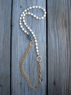 This romantic and feminine necklace features a beautiful faceted labradorite coin shaped bead measuring 20mm wide. Around the neck are white and champagne colored fresh water pearls. With vermeil hammered rings and several strands of gold plated chain. This necklace just slides over your head. Measures 35 inches long.