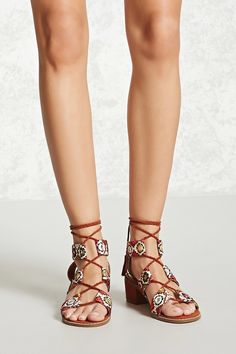 A pair of faux suede shoes featuring embroidered straps with mirrored accents, an ankle wrap with tasseled ends, a faux suede block heel, an open toe, and a crisscross front.
