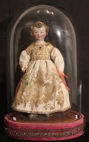 Niño Dios vestido bajo campana de cristal.
