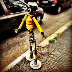 Homem de lata espiando o movimento em frente a uma oficina mecânica na Domingos de Morais.