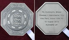 community shield medals - Google Search - silver, shaped like a 50p with a circle shield and England's 3 lions depicted in the centre. Reverse has information about the game, and placing. Fa Community Shield, Bill Shankly, 3 Lions, Aston Villa Fc, Villa Park, Liverpool Fc, Manchester City, Premier League, Centre